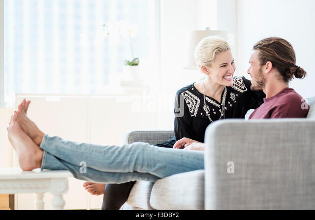 Couple laughing on sofa - Stock Image