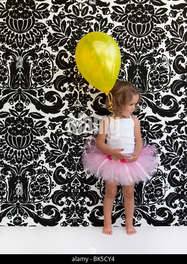 Little girl with pink tutu and yellow balloon - Stock Image