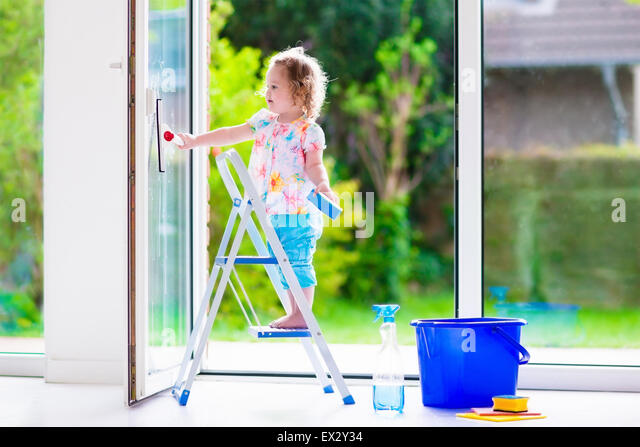 Little girl washing a window. Kids clean the house. Children help at home. Toddler kid cleaning windows and doors - Stock Image