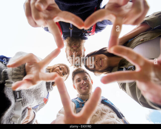 group of smiling friends with backpacks hiking - Stock Image