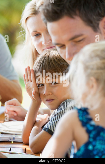 Boy having meal with family outdoors - Stock-Bilder