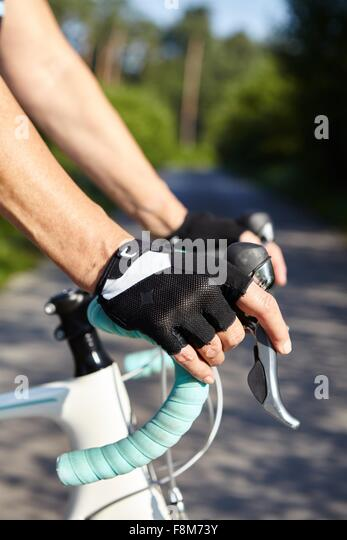 Gloved-hands of cyclist on handle bar - Stock Image