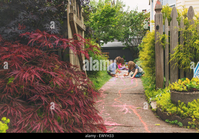 Three young children drawing with chalk on a path in a garden - Stock-Bilder