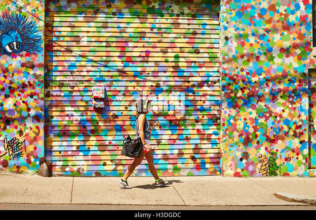 A young asian woman walks past an artistically painted wall. - Stock-Bilder