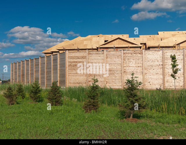New residential houses being constructed behind a noise barrier near a highway. Milton, Ontario, Canada. - Stock Image