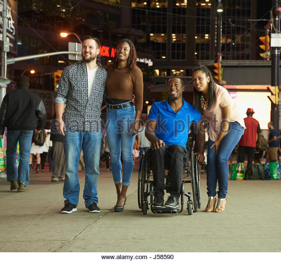 Couples smiling on city sidewalk at night - Stock-Bilder