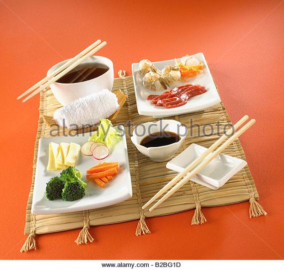 Asian food on mat with chopsticks - Stock Image