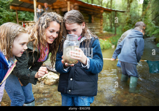 Family looking at insects in jam jar - Stock Image