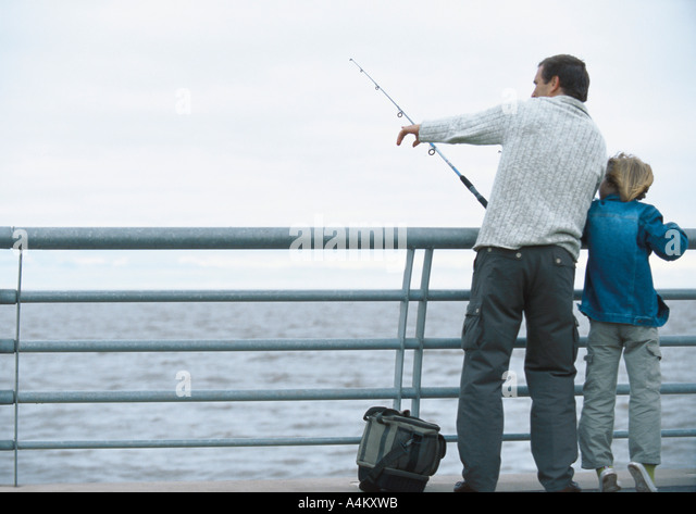 Man and son fishing on pier, man pointing, full length - Stock Image