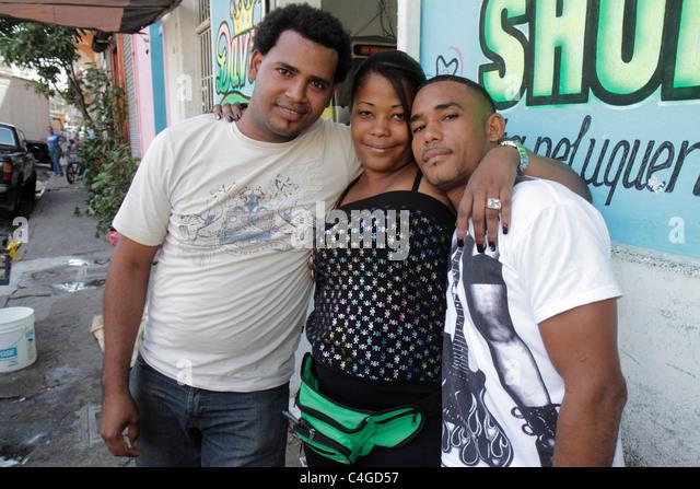 Santo Domingo Dominican Republic Ciudad Colonia Mercado Modela Hispanic Black sidewalk two men one woman pose for - Stock Image
