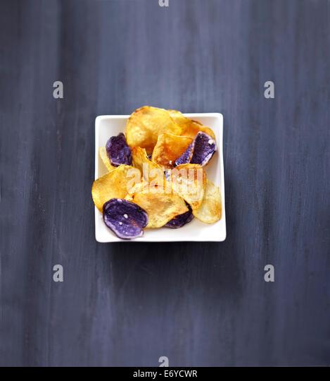 Potato and purple potato crisps - Stock Image