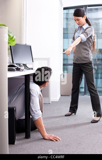 Businesswoman angrily pointing and accusing her colleague hiding under a table - Stock Image