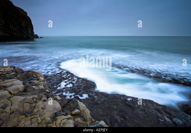 Waves surge into a large rock pool on Dancing Ledge, Purbeck, Dorset - Stock Image
