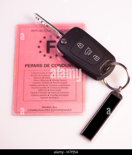 Car keys and drivers license on white background, France - Stock Image
