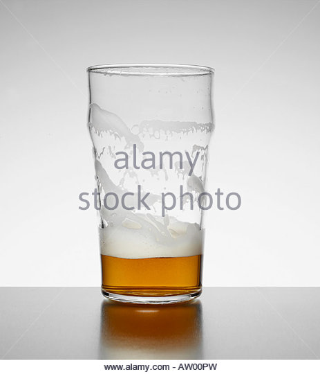 Almost empty glass of beer indoors - Stock Image