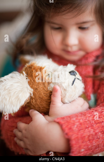 Little girl hugging toy dog - Stock Image