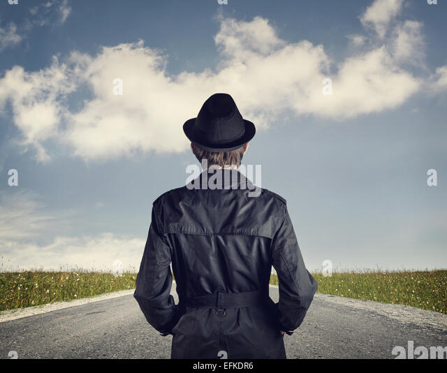 Man in black hat on the road at blue cloudy sky background - Stock Image