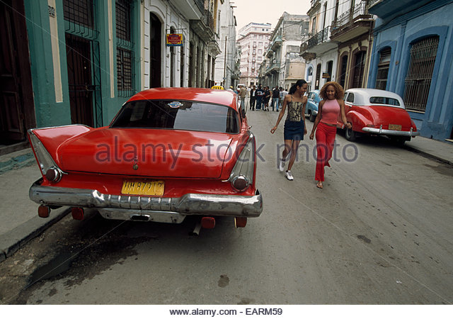 Two girls walk down a street where vintage American cars are parked. - Stock Image