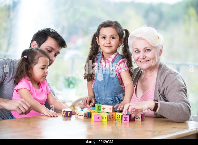 Happy three generation family playing with alphabet blocks at home - Stock Image