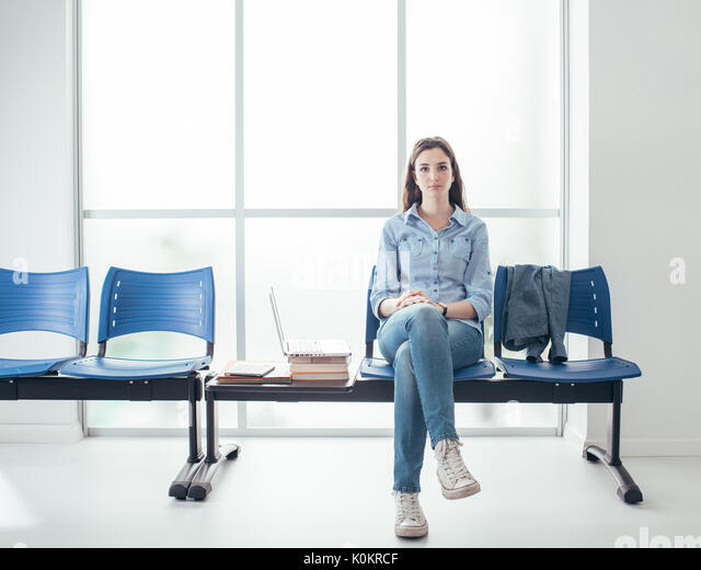 Young female student in the waiting room, she is pensive and waiting for an interview - Stock Image