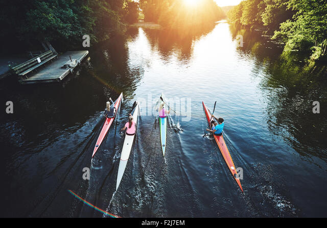 Team of rowing people racing in the sunset - Stock-Bilder