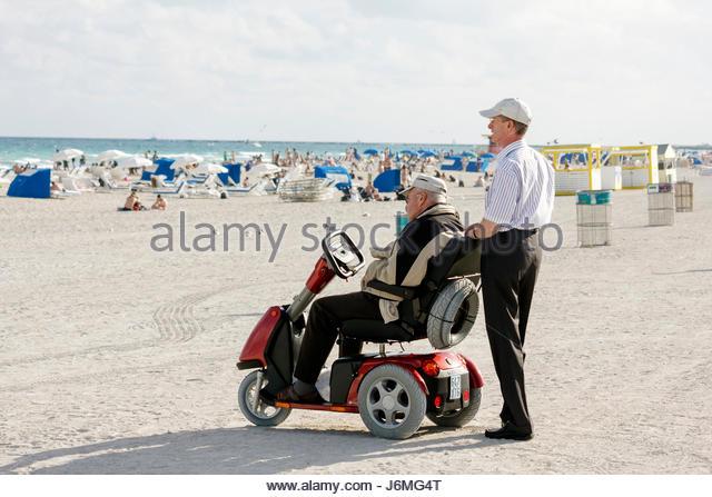 Miami Beach Florida Atlantic Ocean shore man men senior electric wheelchair cart disabled - Stock Image