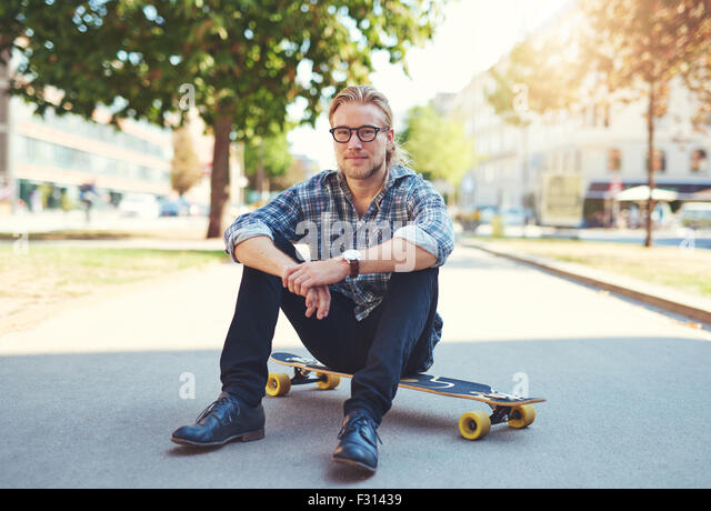 Outdoor portrait of modern young man in the street - Stock Image