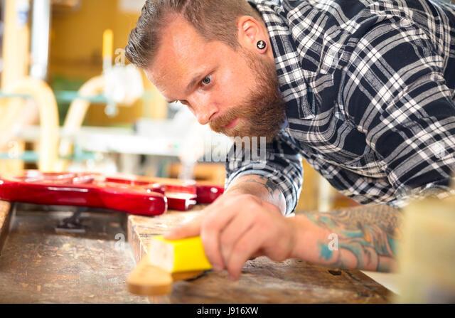 Carpenter sanding guitar neck in wood at workshop - Stock-Bilder