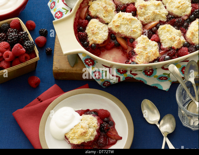 Mixed berry cobbler with strawberries, blackberries and raspberries served with a dollop of cream on a blue background - Stock Image