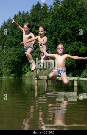 three children jumping into lake - Stock Image