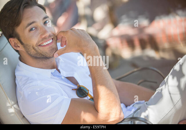 Smiling man relaxing outdoors - Stock Image