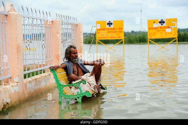 Allahabad, India. 16th July, 2016. A sadhu sit on a chair submerged with flooded water or River Ganga. © Prabhat - Stock Image