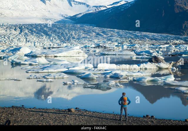 Person beside Fjallsarlon iceberg lagoon, beneath Fjallsjokull glacier, Sudhurland, Iceland. - Stock-Bilder