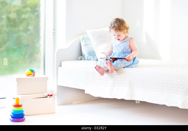 Adorable toddler girl reading a book sitting on a white bed at a big window with garden view - Stock Image