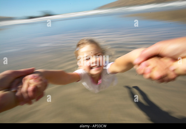 Girl (5 y.) turning around her father (flying merry go round), at Okains Bay, Bank`s Peninsula, east coast, South - Stock-Bilder