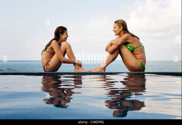Mother and daughter at edge of pool - Stock Image