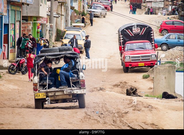 People in a jeep on a unpaved street in Ciudad Bolivar, district of Bogota, Colombia. - Stock Image