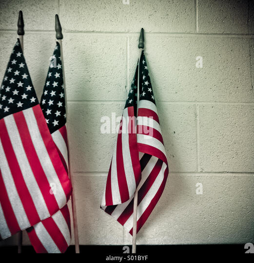 Three American flags lean against a white wall - Stock-Bilder
