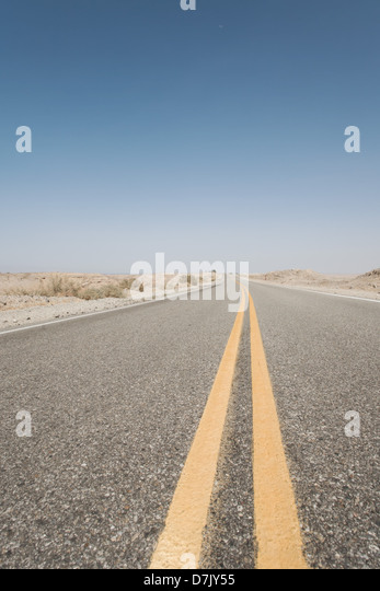 Never ending empty road with dividing yellow lanes in California - Stock Image