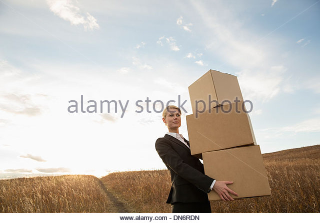 Businesswoman carrying stacked cardboard boxes outdoors - Stock Image