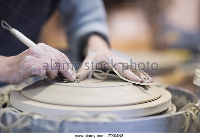 Close up of female potters hands finishing clay plate on pottery wheel - Stock Image