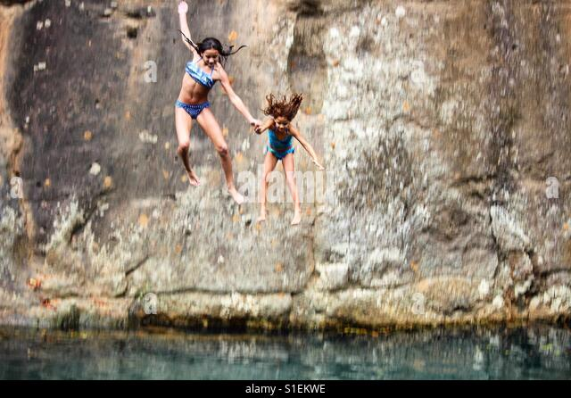 Two girls, holding hands while jumping off of a cliff into a river - Stock Image