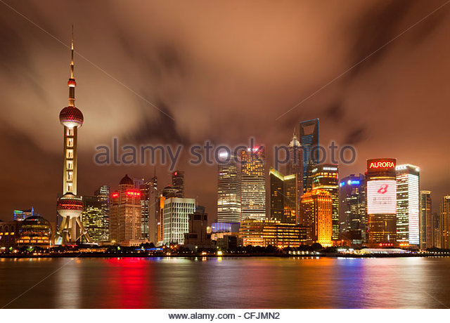 City skyline at night with Oriental Pearl Tower and Pudong skyscrapers across the Huangpu River, Shanghai, China, - Stock Image