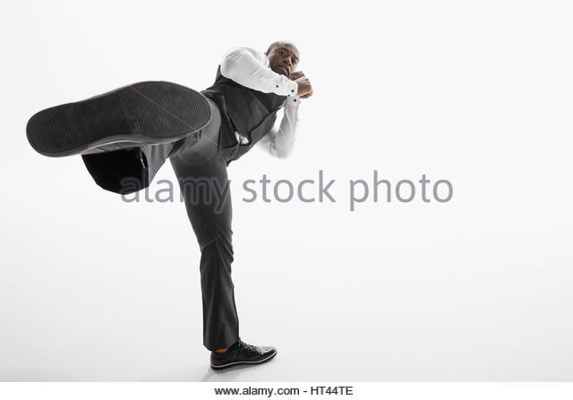 Portrait tough businessman kicking in fighting stance against white background - Stock-Bilder