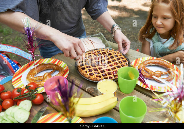 Mother serving food for her daughter at picnic, Munich, Bavaria, Germany - Stock Image