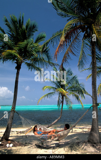 Tropics tropical couple in hammock palm trees beside blue green water blue sky background iconic caribbean image - Stock Image
