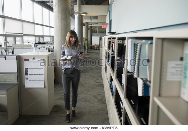 Businesswoman with tray of coffee texting with smart phone in office corridor - Stock Image