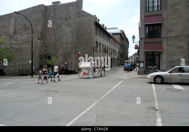 Family crossing street at Rue Ste. Paul Est and Boulevard Saint-Laurent with horse and carriage Montreal Quebec - Stock Image