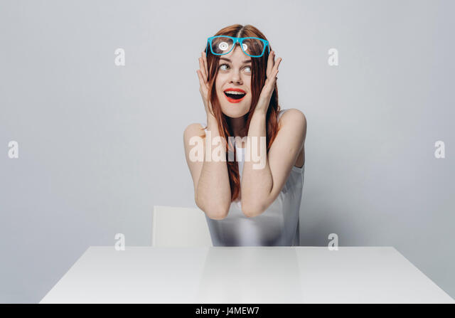 Happy Caucasian woman sitting at table lifting blue eyeglasses - Stock-Bilder