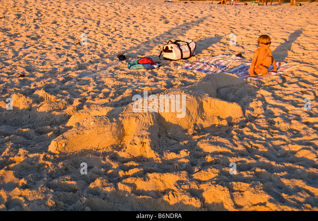 toddler beach alligator sand sculpture Naples Municipal Beach Naples Florida fl late afternoon sunbathers soft light - Stock Image